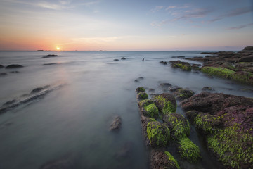 Beautiful sunset decorated with waves and mosses stone