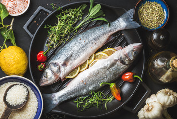 Ingredients for cookig healthy fish dinner. Raw uncooked seabass fish with rice, lemon, herbs and spices on black grilling iron pan over dark background, top view, horizontal composition