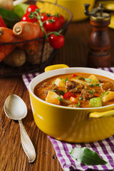 Beef stew served with cooked potatoes.