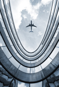 Modern architecture building with flying airplane in background. Low angle view blue colorized picture