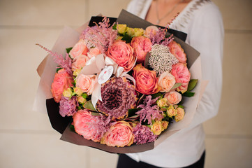 Bouquet of different mixed orange flowers in woman hands