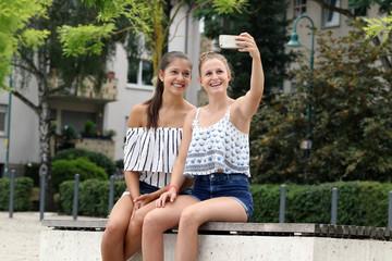 Lachende junge Frauen sitzen auf einer Bank im Park und machen ein Selfie mit ihrem Smartphone