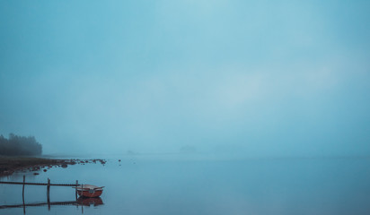 Lone rowing boat by a small jetty in late night mist up in northern Sweden, Scandinavia. On a silent lake. Wide shot.
