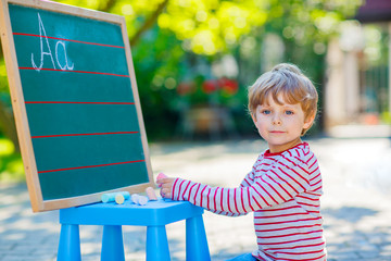 Little boy at blackboard practicing letters