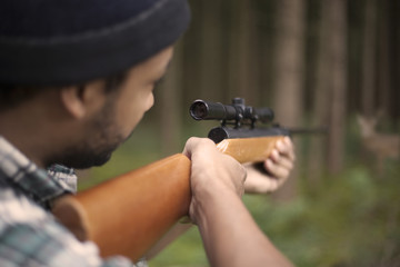 Interracial hunter in the forest aiming at prey