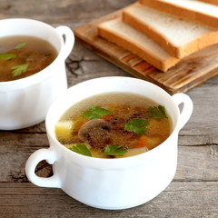 Easy mushroom soup with potatoes, carrots and parsley in bowls. Soup cooked in agaricus broth with vegetables. Traditional dish of Russian cuisine. Bread slices on wooden board