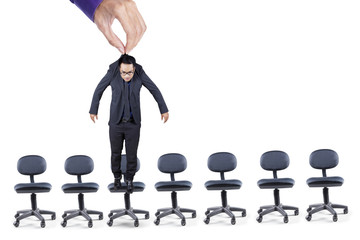 Businessman hangs over office chairs