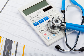 Health care costs. Stethoscope and calculator
