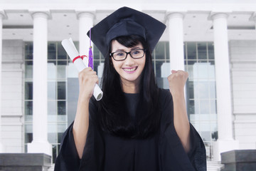 Happy student with mortarboard in campus