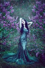 pretty slim girl with dark hair in a long emerald green dress wi