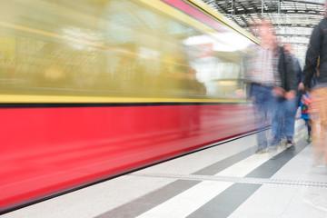 Commuters walking on platform, motion blurred train