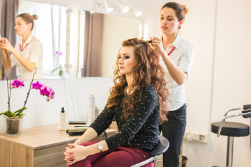 Professional hairdresser styling woman curly hair.