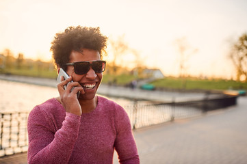 Portrait of a smiling guy using mobile phone.