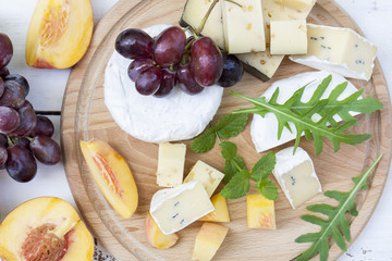 Different delicious cheeses camembert, blue cheese, cheese with nut, fruits red grapes and peach and herbs mint and arugula on wooden round board