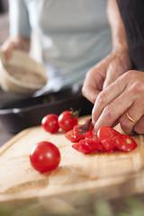 Männerhände beim Tomatenschneiden