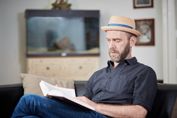 Man with beard and hat reads a book at home