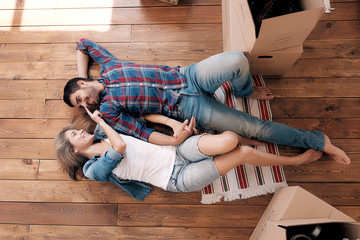 Smiling married couple lying on floor in new home