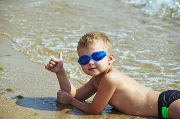 A fun , happy boy on the beach , glasses for swimming .