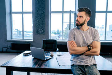 Bearded businessman with arms crossed at desk