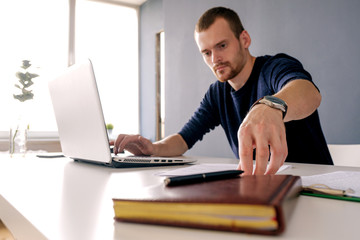 Businessman taking document at desk with laptop