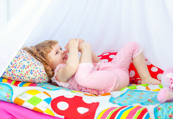 Little cute curly girl in pink pajamas lying in a baby bed