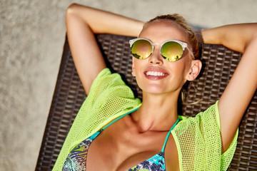 Beautiful tanned bonde woman in bikini sunbathing