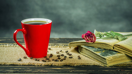 Various objects on a wooden table. Coffee cup, withered roses and old books
