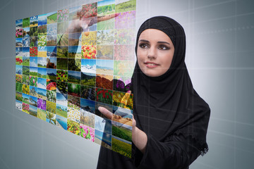 Arabian woman pressing virtual button on nature collage