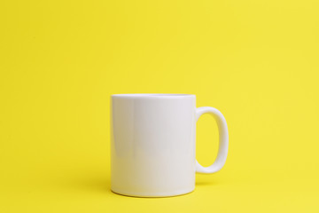 White coffee cup on yellow background.