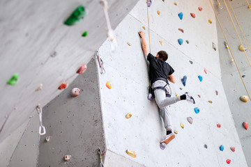 man climbing on artificial boulders wall indoor, rear view