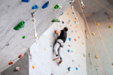 man climbing on practical wall indoor, securing carabiners and rope