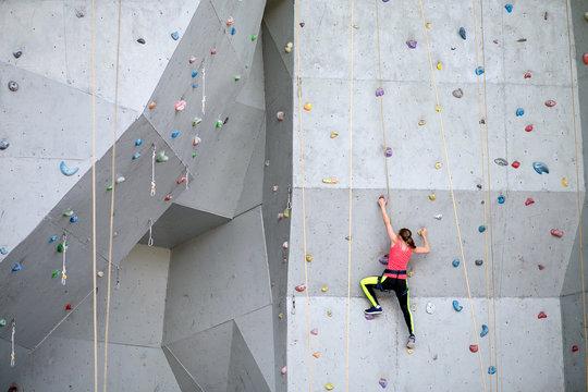 Beautiful young woman starts to climbing big artificial wall