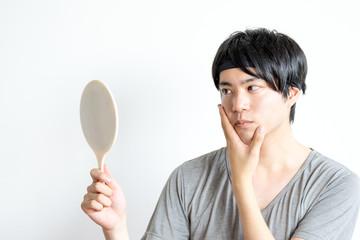 鏡を見る男性(美容イメージ)