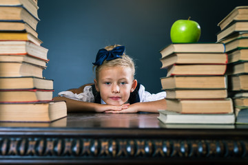 Closeup school girl sitting at the table with many books