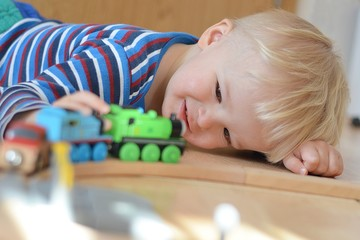 Smiling boy playing with a locomotives