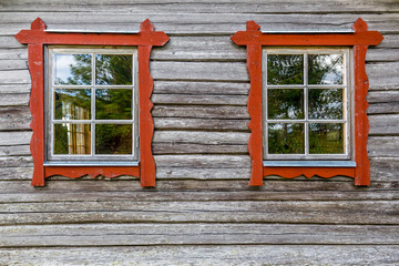 Two windows with red frames on log house wall, traditional style.