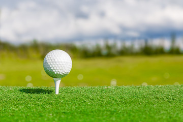 Close up of golf ball and tee with with blurred background.