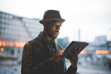 Portrait of young handsome afro black man using a tablet, looking downward the screen, pensive - technology, social network, communication concept