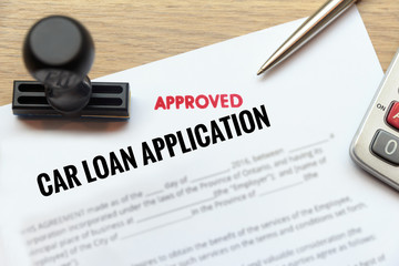 Approved car loan application form lay down on wooden desk
