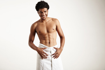 young latin man in white towel is smiling