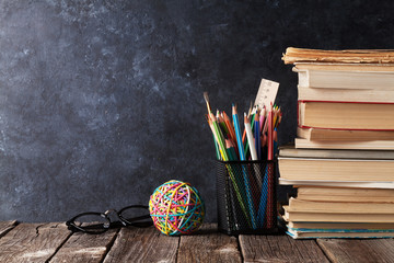 Books and supplies in front of chalk board