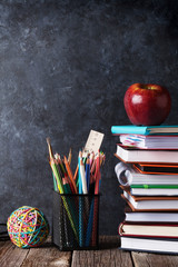 Notepads, supplies and apple in front of chalk board