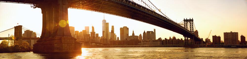 Manhattan skyline panorama under Manhattan Bridge at sunset, New York