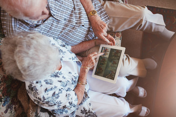 Senior couple looking images on digital tablet