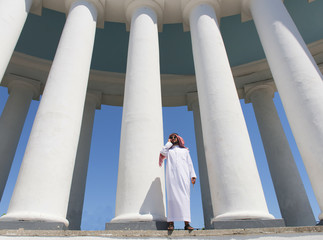 Arabian man standing in front of large columns, view from below