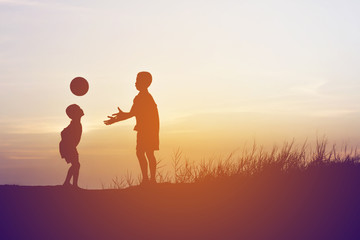 children playing ball on meadow, sunset, summertime