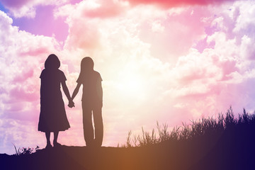 silhouette of two girls facing each other hold hands together