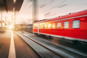 Modern high speed red passenger train moving through railway station in the evening. Railway station at sunset in Nuremberg, Germany. Railroad with motion blur effect. Industrial concept landscape