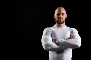 Young powerful sportsman in white clothing over black background.