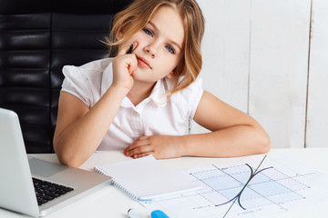Young beautiful girl sitting at working place in office.